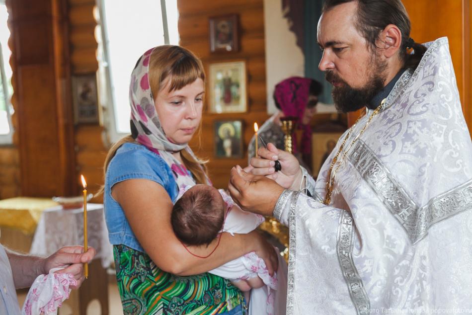 Женщина на крещении ребенка, батюшка читает над ней разрешительную молитву