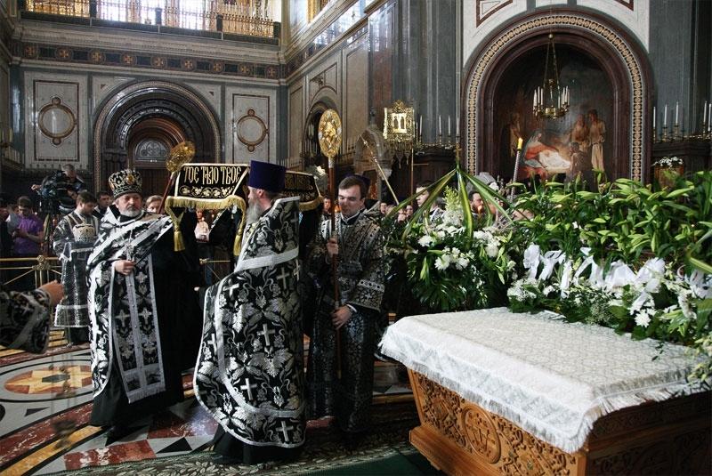 Священнослужители в черных одеждах выносят плащаницу