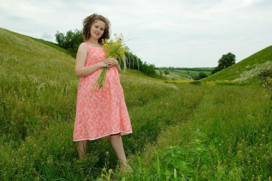 Счастливая беременная девушка собирает травы и не страдает циститом