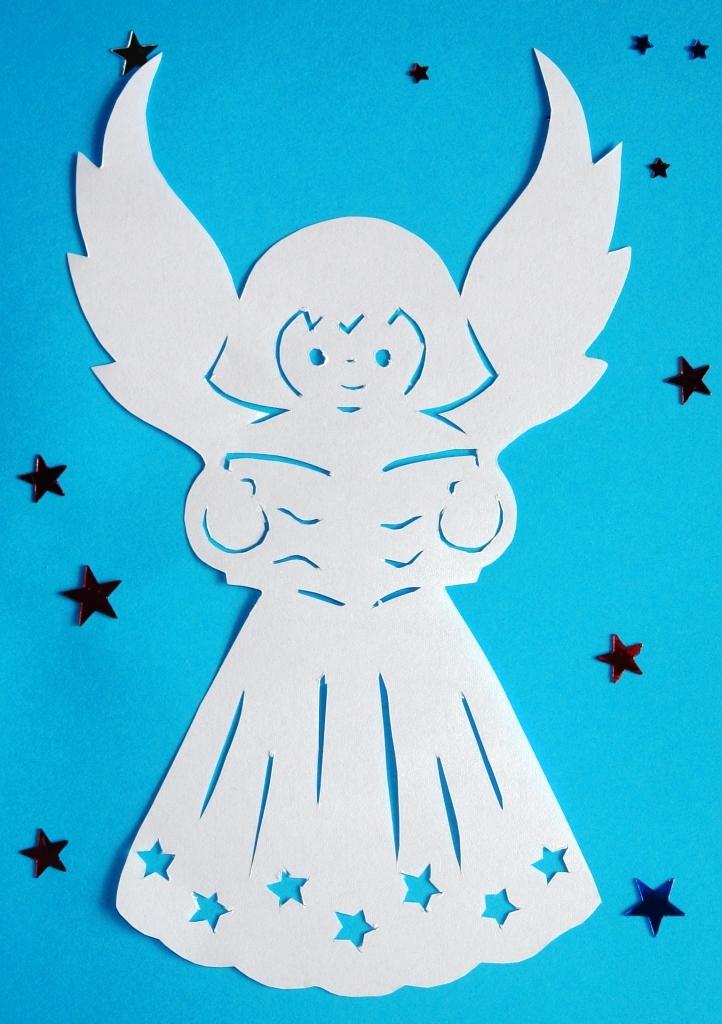 Вырезанный из белой бумаги новогодний ангел
