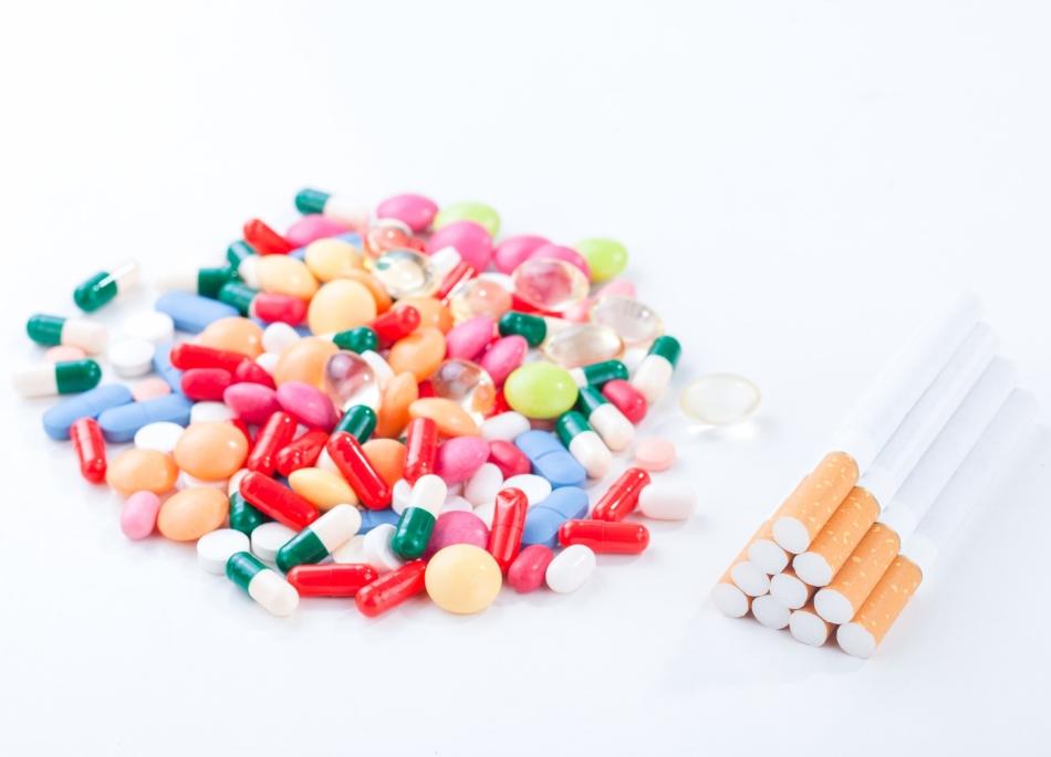 Гора разных таблеток и капсул антидепрессантов при отказе от курения рядом со стопкой сигарет