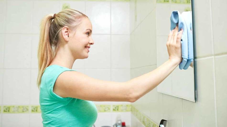 Девушка моет зеркало в ванной