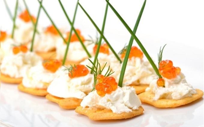 Вариант оформления канапе с красной икрой: соленый крекер, сливочный сыр, икра, зелень