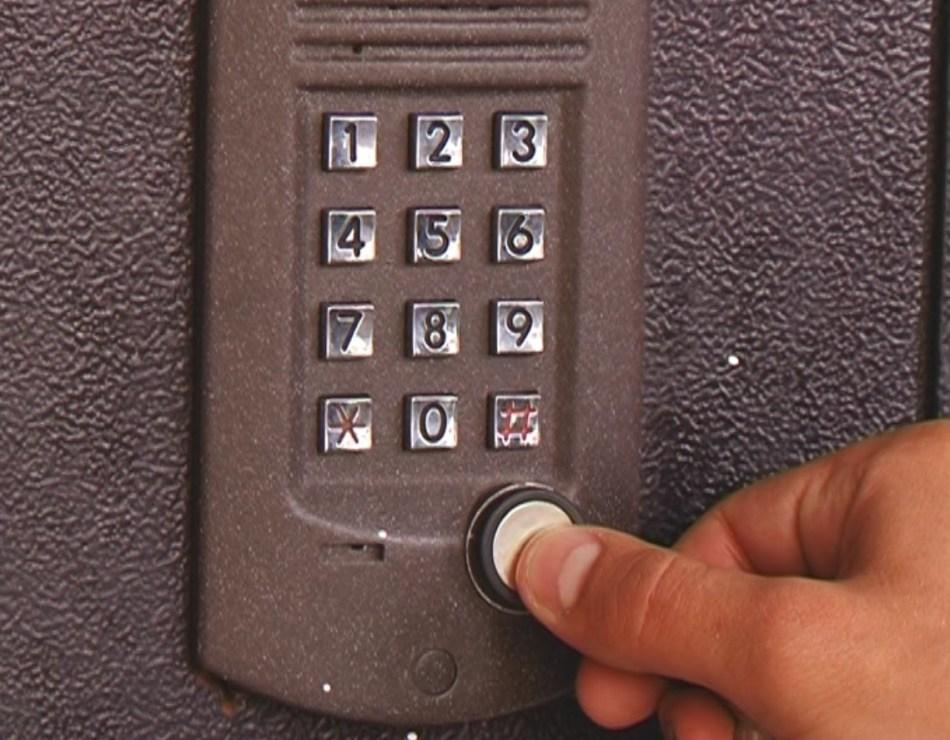 Человек завершает ввод кода кнопкой вызова на домофоне