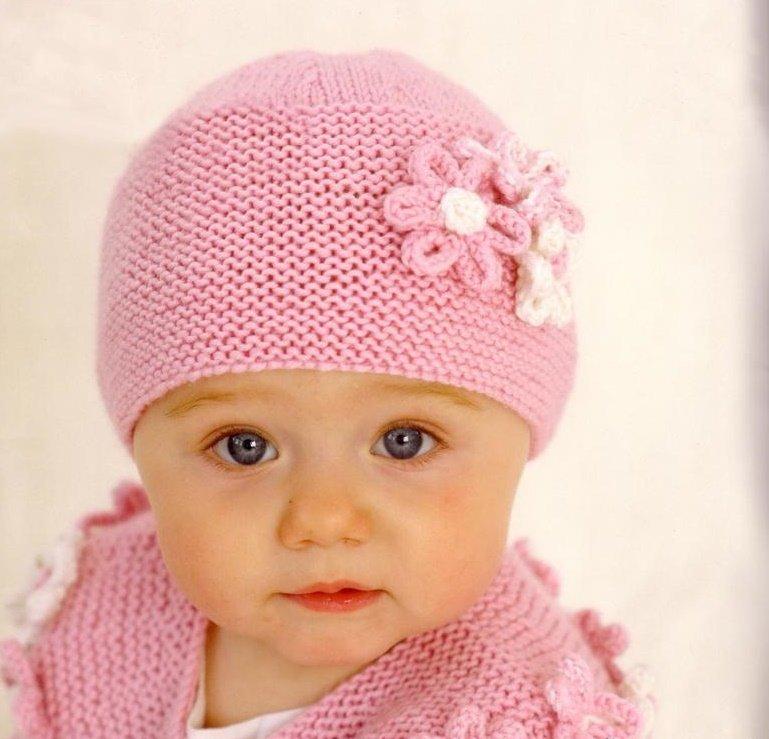 Розовая вязаная спицами шапка с цветком на маленькой девочке