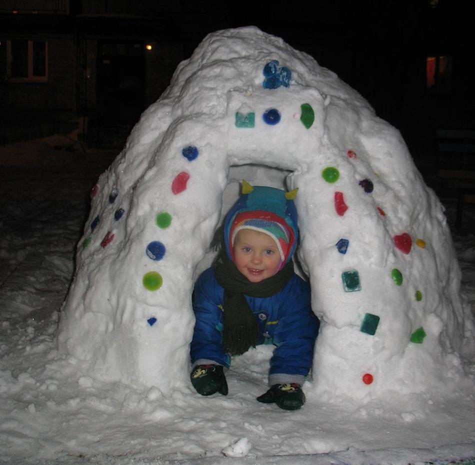 Украшенная игла, вылепленная из снега, из которой выглядывает малыш