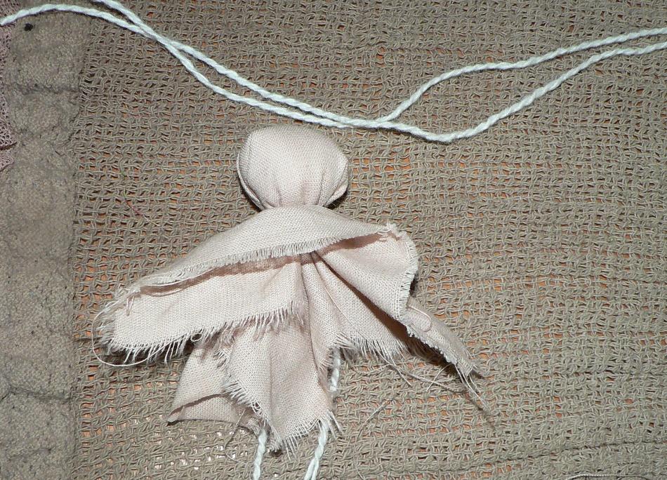 Ткань под головой куклы-оберега расправляется
