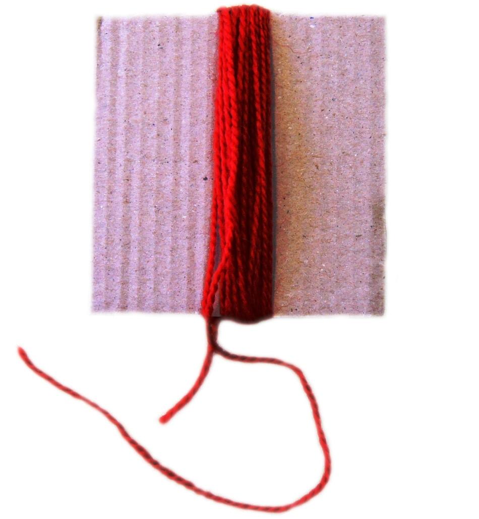 Для создания туловищ куклы-оберега красная пряжа наматывается на картонку