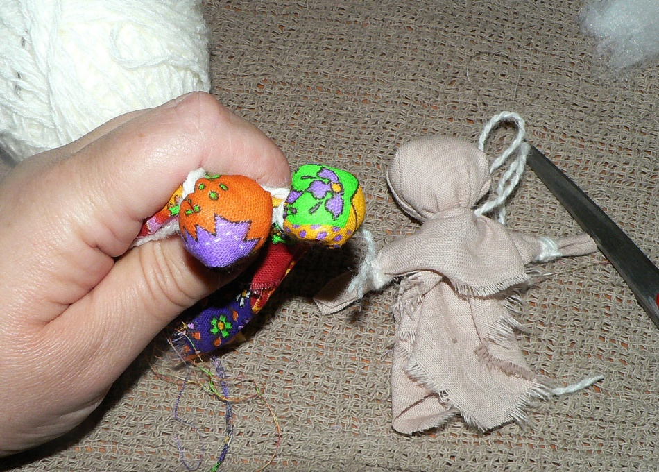 Грудь из яркой ткани для куклы-оберега скрепляется ниткой