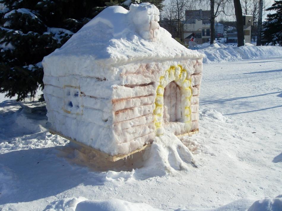 Симпатичный домик из снега стоит во дворе
