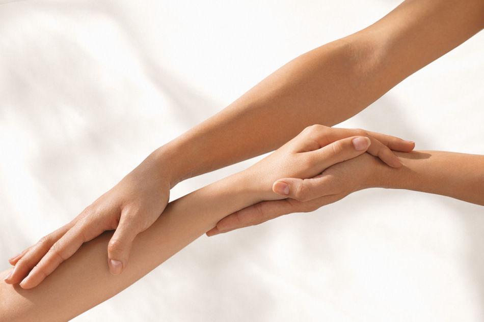Девушка разминает больную руку другого человека