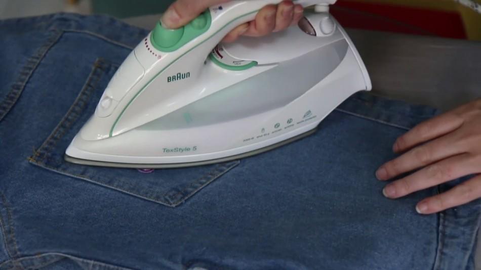 Девушка приклеивает заплатку на джинсы с помощью утюга